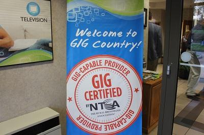 "A sign featuring a round, orange logo that reads, ""Gig Certified by NTCA."""